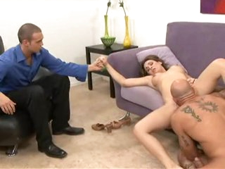 Holly West munches on a monster cock while her tighten one's belt watches.