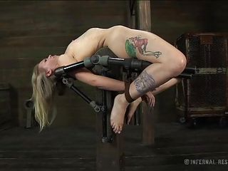 tattooed golden-haired on a bondage device