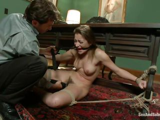 Ball gagged and fastened on the table the cute chick cries and moans as the man rubs her hairy pussy with a vibrator. He grabs her firmly by the hair and continues until she's abandoned for a short period of time. In the next scene she's still fastened on the table but bent over, slapped and screwed in that gorgeous ass