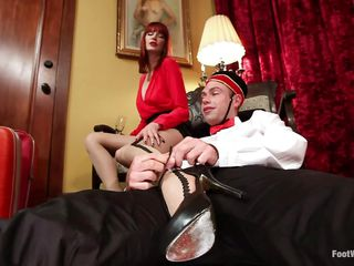 Maitresse Madeline makes bellhop John Jammen remove her high heels and sniff her nylon-covered feet. She rubs her hose all over his cock, and the feet pervert loves it. His hairy pouch is red and swollen from the torture. After receiving his feetjob, Madeline allows him to lick her pussy.