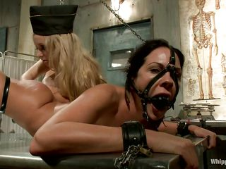 Aiden and Kirsten are two captivating milfs that know how to have a lot of pleasure together. The brunette hair is fastened on a table and gets a deep fisting in her shaved pussy from the blonde one and a vibrator on her clitoris making her moan wildly. After the ball gag is removed she licks Aiden's cunt.