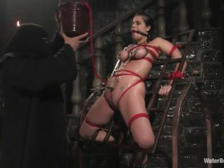 Mia Bangg is bound and gagged in the dungeon where her torturer sprays her nipple-clamped tits. This chab asks if she wishes to get fucked and she does, but first he gives her a little more pain by pulling tight the rope that splits her vagina lips and smacks her cunt previous to using a dildo on her.