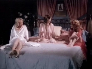 Three girls in night gowns are sitting on a bed, talking to each other. Two of 'em begin to make love with one another while the third one watches them. Finally she takes her clothes off and joins in, having her tits and her pussy licked.