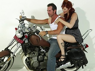 A redhead that has large jugs is obtaining fucked on rub-down the bike