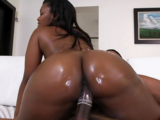 Ebony girl relating to a giant ass is riding a massive black cock here