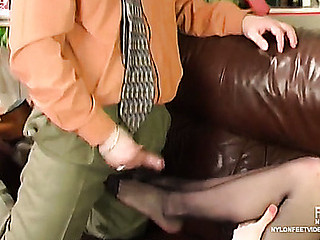 Female co-worker in black pantyhose starts her working day with giving footjob