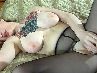 Tattooed hottie clad in crotchless little short of black pantyhose fucking a rubber dong