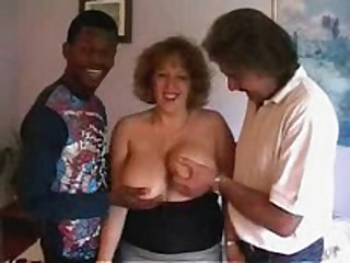 Stylish crumpet with biggest soft melons gets ready to satisfy even two rock hard dicks! She sucks both rods and moves on 'em furiously!