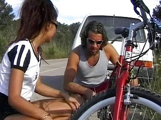 Cute brunette cracks down on her bike and blows and pokes the dude who stops for her