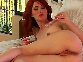 Redhead hottie Elle Alexandra enjoys stimualting her doting clit with her favorite dildo